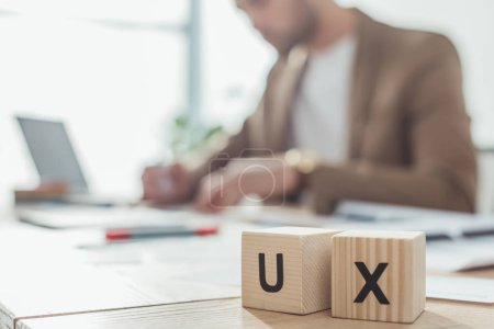 Selective focus of wooden cubes with ux letters and creative designer working at table