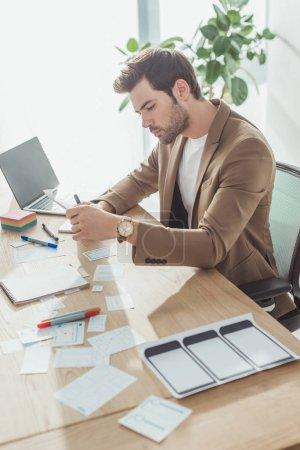 Photo pour Vue latérale du concepteur créatif faisant des croquis de l'interface de l'application à la table de bureau - image libre de droit
