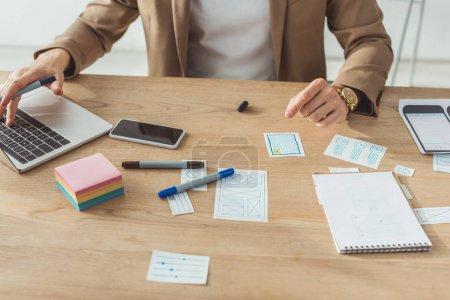 Photo pour Vue recadrée du concepteur à l'aide d'un ordinateur portable tout en planifiant des croquis pour l'interface d'application mobile à la table - image libre de droit