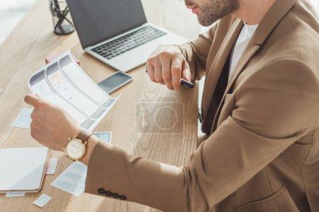 Photo pour Vue agrandie d'un concepteur tenant des croquis de cadres filaires pour un site Web mobile à côté d'un ordinateur portable et d'un téléphone intelligent sur une table - image libre de droit