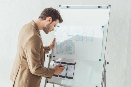 Photo pour Vue latérale du concepteur créatif prenant des notes de l'interface de l'application sur le tableau blanc au bureau - image libre de droit
