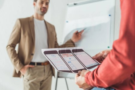 Photo for Selective focus of designer holding ux mobile application layout with colleagues beside whiteboard at background - Royalty Free Image