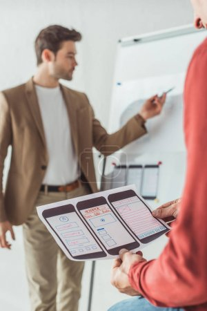 Photo for Selective focus of creative designer holding mobile website sketches while colleague whiting on whiteboard in office - Royalty Free Image