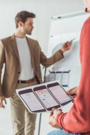 Photo pour Concentration sélective du concepteur créatif tenant des esquisses de site Web mobile tout en collègue merlan sur tableau blanc dans le bureau - image libre de droit