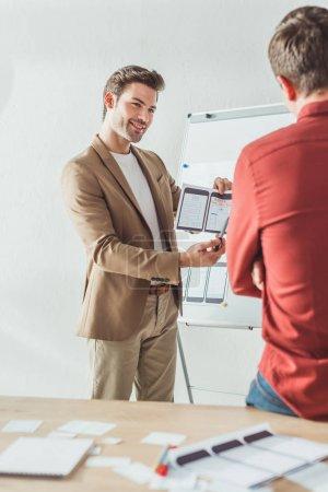 selektiver Fokus des lächelnden Designers, der dem Kollegen im Büro Bildschirme der mobilen ansprechenden Website-Entwicklung zeigt