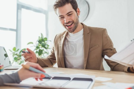 Photo for Selective focus of smiling ux designer developing mobile app prototype with colleague in office - Royalty Free Image