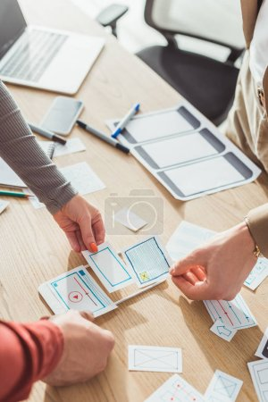 Photo for Cropped view of ux designers with web sketches and mobile protopype working at table - Royalty Free Image