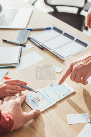 Cropped view of ux designers developing mobile app with layouts on table