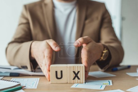 Photo for Cropped view of designer holding wooden cubes with ux letters at table with layouts - Royalty Free Image