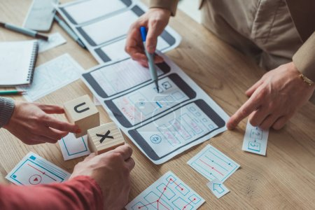 Cropped view of designers with mobile website wireframe sketches and cubes with ux letters on table