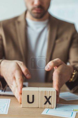 Photo pour Vue recadrée du designer tenant des cubes avec des lettres ux à table avec des croquis - image libre de droit