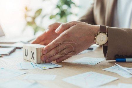 Photo pour Vue recadrée du designer tenant des cubes en bois avec des lettres ux à côté des esquisses de l'application sur la table - image libre de droit