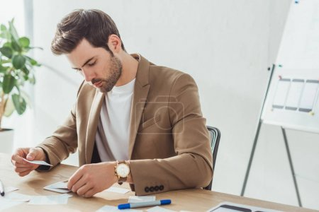 Photo for Handsome creative designer developing user experience design with sketches on table - Royalty Free Image