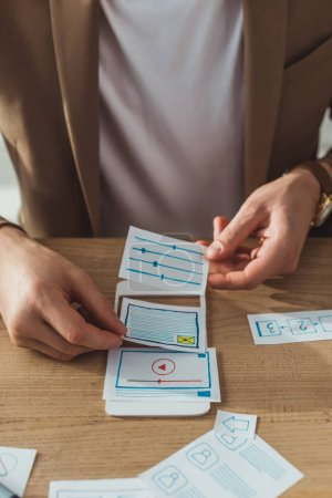 Photo for Cropped view of ux designer working with prototype of mobile app at table - Royalty Free Image