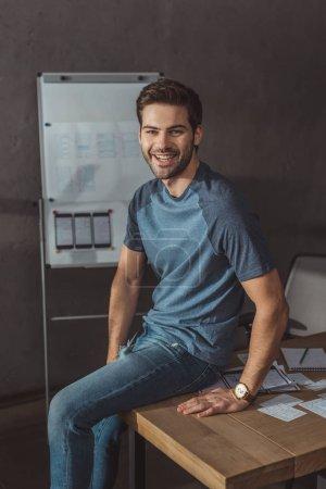 Photo pour Beau ux designer souriant à la caméra assis sur une table avec des croquis - image libre de droit