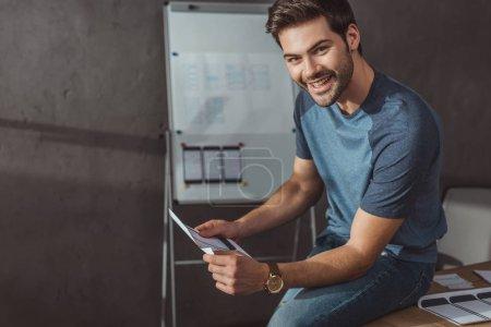 Photo pour Un concepteur sourit à la caméra alors qu'il tient un modèle de site Web mobile en studio - image libre de droit
