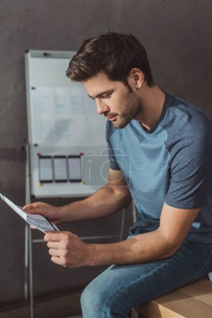 Photo for Side view of designer holding template with mobile wireframe sketches while sitting on table in office - Royalty Free Image