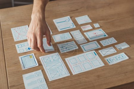 Photo for Cropped view of designer planning user experience design with sketches on table - Royalty Free Image