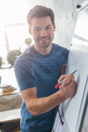 Photo pour Beau développeur qui sourit à la caméra tout en dessinant un modèle de site Web sur tableau blanc au bureau - image libre de droit