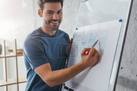Photo pour Point de mire sélectif d'un concepteur souriant regardant la caméra pendant qu'il dessine un modèle de site Web sur tableau blanc au bureau - image libre de droit
