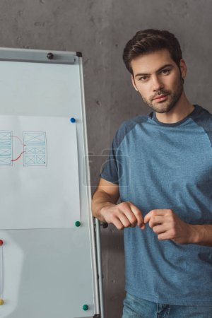 Handsome ux designer looking at camera by website app layouts on whiteboard