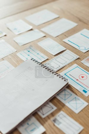 Photo for High angle view of notebook and user experience design sketches on wooden table - Royalty Free Image