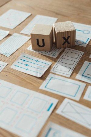 Photo pour Concentration sélective de cubes en bois avec des lettres ux par des esquisses d'application sur la table - image libre de droit