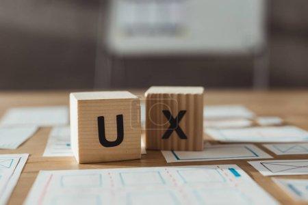 Photo pour Mise au point sélective de cubes avec des lettres X et des croquis d'app designer sur la table - image libre de droit