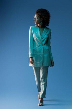 Photo pour Attrayant afro-américain femme en costume regardant loin sur fond bleu - image libre de droit