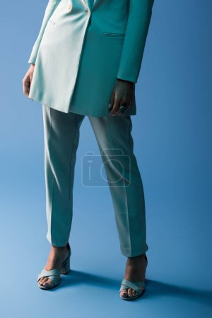 Photo for Cropped view of african american woman in suit on blue background - Royalty Free Image