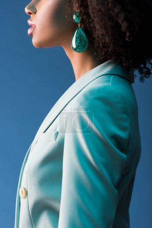 Photo for Cropped view of african american woman in suit and earring isolated on blue - Royalty Free Image