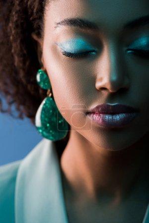 Photo pour Séduisante femme afro-américaine aux yeux fermés et maquillage isolé sur bleu - image libre de droit