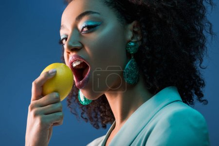 Photo for Attractive african american woman with braces eating lemon isolated on blue - Royalty Free Image