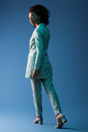 african american woman in suit looking at camera on blue background