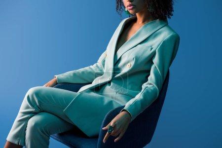 Photo pour Vue recadrée de femme afro-américaine assise sur un fauteuil isolé sur bleu - image libre de droit