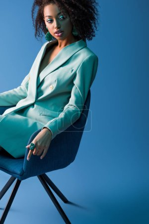 Photo for African american woman sitting on armchair on blue background - Royalty Free Image