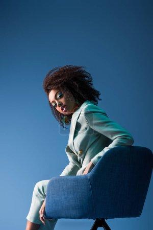 Photo pour Afro-américaine assise sur un fauteuil isolé sur bleu - image libre de droit