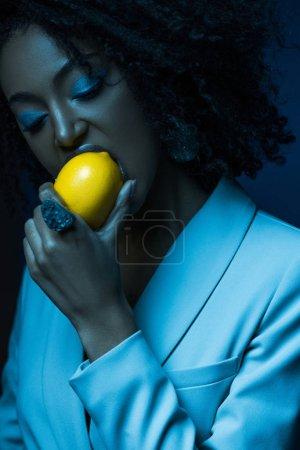 Photo pour Attrayant afro-américain femme avec maquillage manger citron isolé sur bleu - image libre de droit