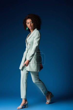 Photo pour Séduisante femme afro-américaine marchant sur fond bleu - image libre de droit