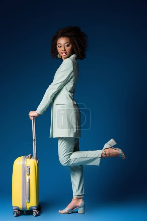 smiling african american woman holding travel bag on blue background