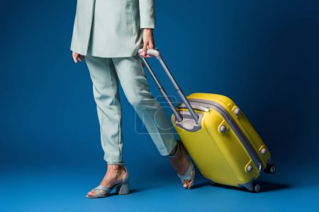 cropped view of african american woman holding travel bag on blue background
