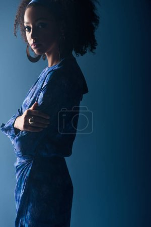 Photo for Attractive african american woman looking at camera on blue background - Royalty Free Image