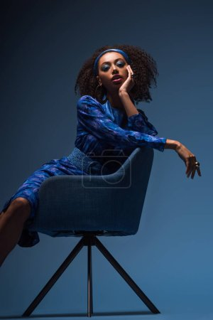 Photo pour Attrayant afro-américaine femme assise sur un fauteuil sur fond bleu - image libre de droit
