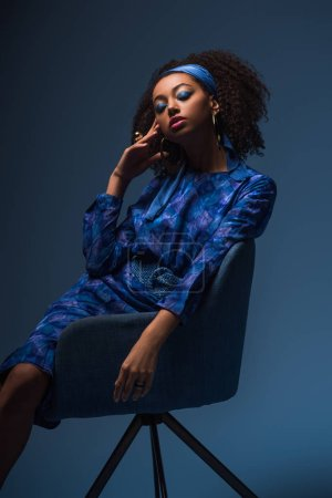 Photo pour Attrayant afro-américain femme avec les yeux fermés assis sur un fauteuil isolé sur bleu - image libre de droit