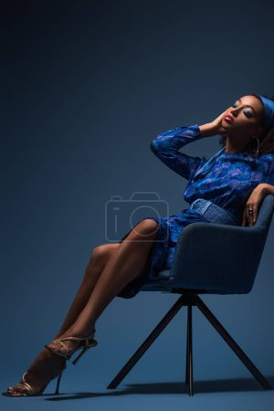 attractive african american woman with closed eyes sitting on armchair on blue background