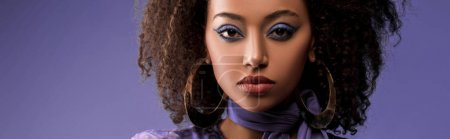 Photo for Panoramic shot of attractive african american woman with earrings looking at camera isolated on purple - Royalty Free Image