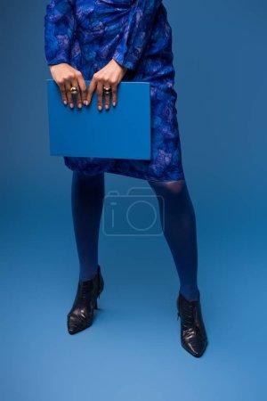 vista recortada de la mujer afroamericana sosteniendo carpeta aislado en azul
