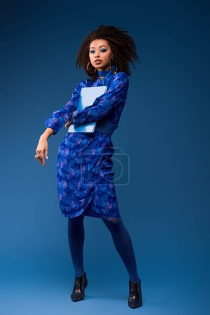 attractive african american woman holding folder on blue background