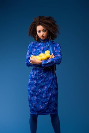 attractive african american woman holding lemons isolated on blue