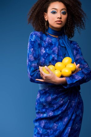 attraktive afrikanisch-amerikanische Frau hält Zitronen isoliert auf blau